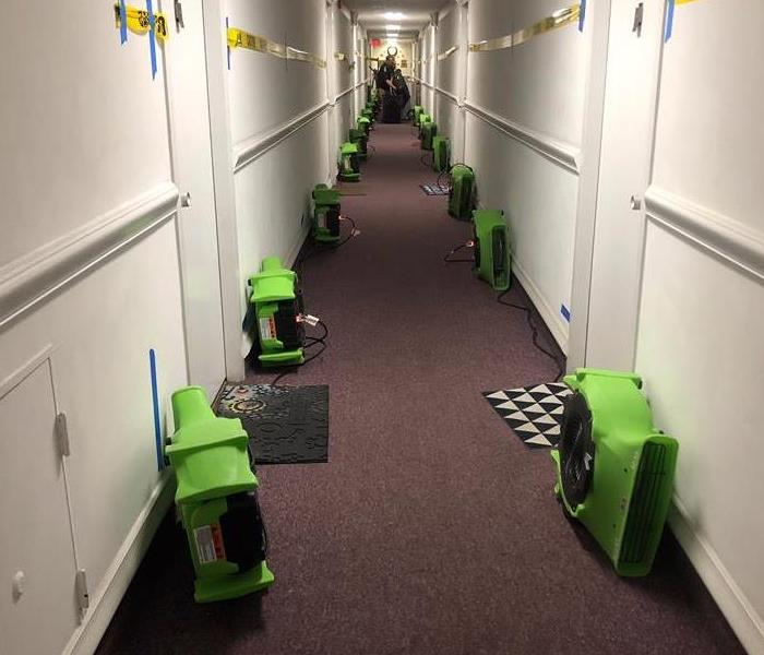 Hallway with green SERVPRO air movers.