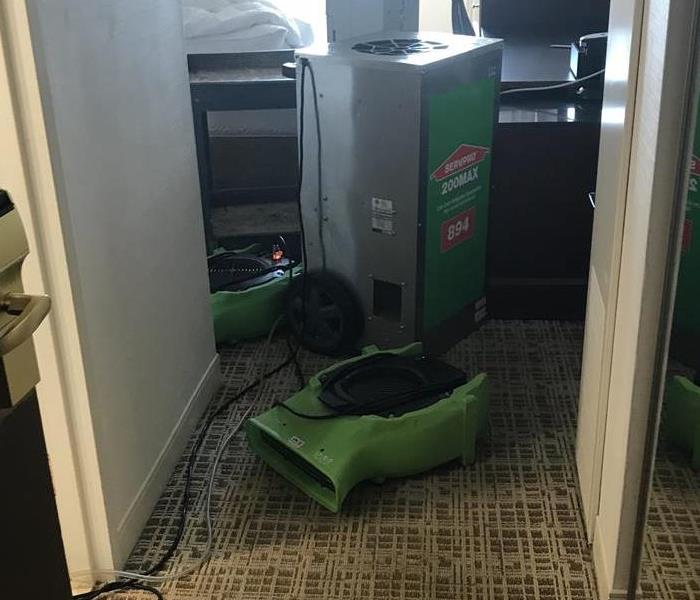 Green air mover on the floor in front of a dehumidifier.