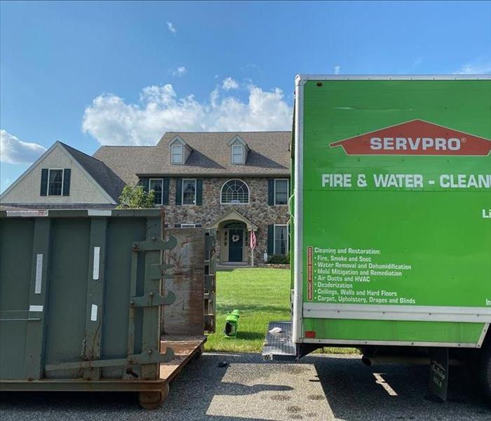 SERVPRO truck and dumpster outside of a brick home.