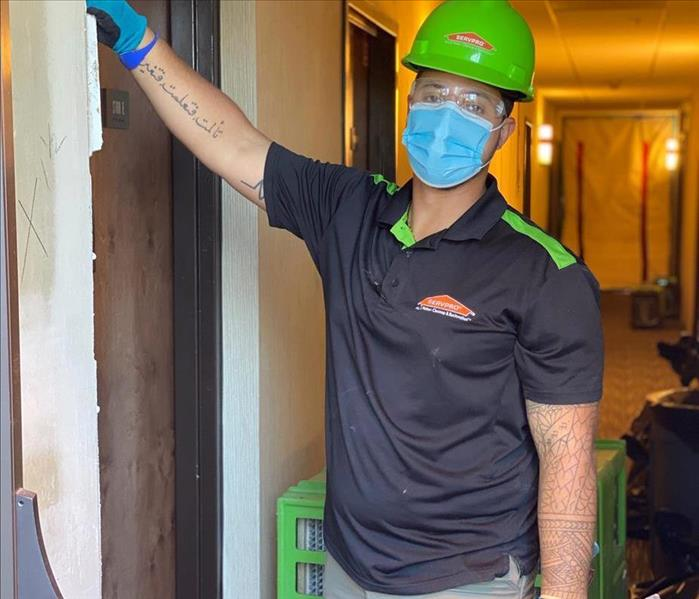 Tall male employee posing for a photo in a green hard hat.