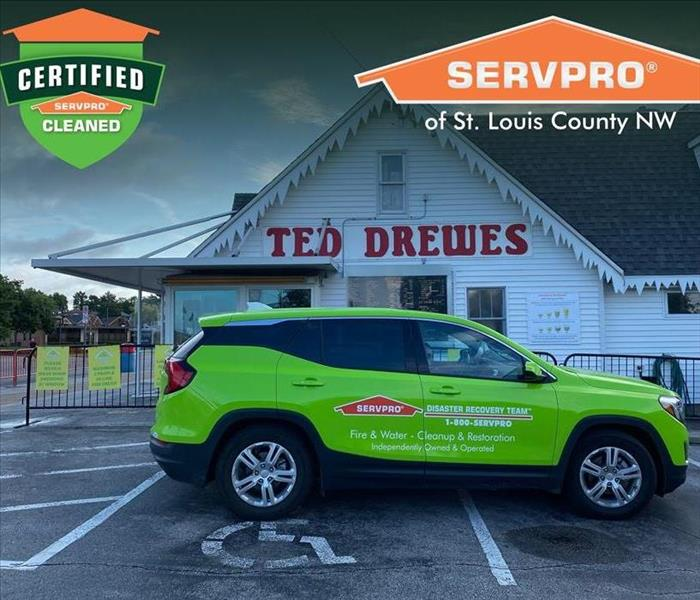 Green SERVPRO SUV parked in front of Ted Drewes.